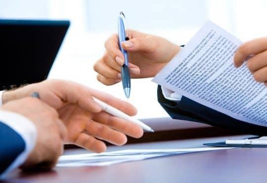 Deux personnes qui signent des papiers